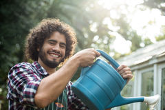 Happy gardener watering outside greenhouse Stock Photo