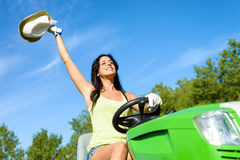 Happy gardener working with garden tractor. Successful woman riding green garden tractor. Happy female gardener driving and working with lawn mower for summer Royalty Free Stock Photography