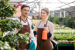 Happy gardeners holding watering can and pulveriser for spraying flowers Stock Photo