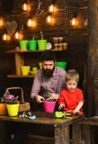 Happy gardeners with spring flowers. Family day. Greenhouse. Flower care watering. Soil fertilizers. Father and son. Bearded men and little boy child love stock images
