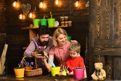 Happy gardeners with spring flowers. Family day. Greenhouse. Flower care watering. Soil fertilizers. Father and son with. Mother. woman, men and little boy stock photography
