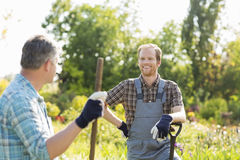 Happy gardeners talking at plant nursery Royalty Free Stock Photo