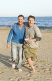 A happy gay couple. A homosexual couple are fooling around on the beach during their vacaton Stock Images