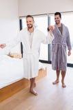 Happy gay couple dancing in bathrobe Stock Images