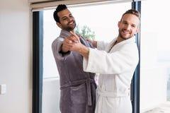 Happy gay couple dancing waltz in bathrobe Royalty Free Stock Photo