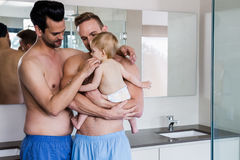 Happy gay couple holding their child Stock Images