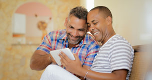 Happy Gay Couple Homosexual People Men Using Tablet. Homosexual couple, hispanic gay men laughing while looking at pictures on tablet pc at home Royalty Free Stock Photo