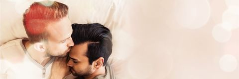 Happy gay couple lying on bed. At home Stock Photo
