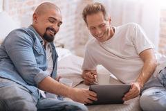 Happy gay couple lying on the bed and having fun. We having fun together. Smiling positive cheerful non-traditional couple lying on the bed and drinking tea Royalty Free Stock Image