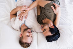 Happy gay couple lying on bed Royalty Free Stock Photo