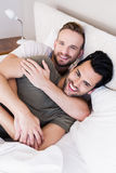 Happy gay couple lying on bed Stock Photography