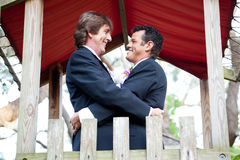 Happy Gay Couple Marries in the Park. Happy gay couple getting married on the playground of a park Royalty Free Stock Photography