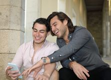 Happy gay couple smiling with their mobile phone stock photography