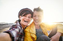 Happy gay couple taking selfie on the beach at sunset - Young lesbians having fun dating first time - Lgbt, homosexuality love royalty free stock photos