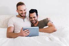 Happy gay couple using tablet. In bed Royalty Free Stock Photo