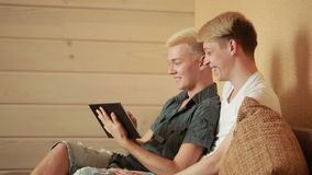 Happy gay couple using tablet in bed. gay couple stock video