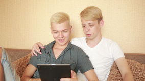 Happy gay couple using tablet in bed. gay couple. Happy gay couple using tablet in bed stock video