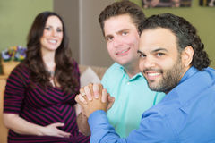 Happy Gay Parents with Pregnant Woman Stock Image