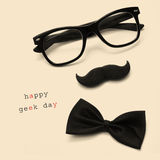 Happy geek day. A pair of glasses, a mustache, a bow tie and the sentence happy geek day on a beige background Stock Photos