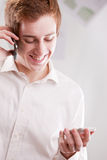 Happy geek with two mobile phones. A happy geek man with two mobile phones or smartphones Royalty Free Stock Photo