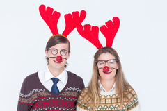 Happy geeky hipster couple with stag headband Royalty Free Stock Photos