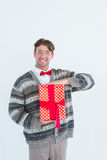 Happy geeky hipster with wool jacket holding present. On white jacket stock photo
