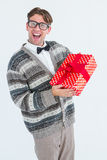 Happy geeky hipster with wool jacket holding present. On white jacket royalty free stock photos