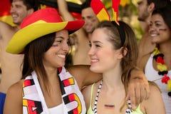 Happy German women sport soccer fans celebrating victory. Happy German women sport soccer fans celebrating victory hugging each other Royalty Free Stock Photos