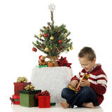 Happy with Gift. A barefoot preschooler happily opening a small Christmas gift by his tiny Christmas tree.  On a white background Stock Photo