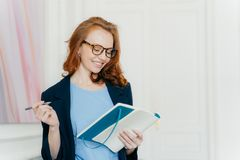 Happy ginger young female plans working schedule, writes in notebook, makes notes of useful information, holds pen, has smile on stock image