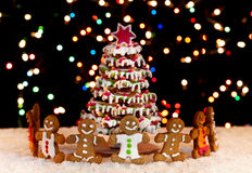 Happy gingerbread people around the christmas tree Royalty Free Stock Photo