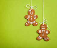 Happy Gingerbread People on Green. Gingerbread cookies hanging by twine over a green, textured paper background stock images