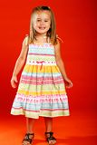 Happy girl. Cute little girl wearing sundress set against orange backdrop Stock Photo