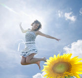 Happy girl. A happy girl. Sunflower and sky Royalty Free Stock Image