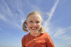 Happy girl. Young girl smiles with her bright teeth against a blue sky royalty free stock image