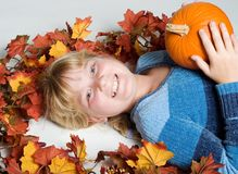 Happy girl. With pumpkin on colorful leaves stock images