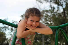 Happy Girl. Happy and confident girl relaxing outdoor on a playground royalty free stock photography