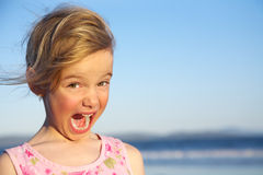 Happy girl. A funny little blond girl making a surprised face with her mouth open stock images
