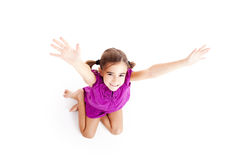 Happy girl. Top view of a happy girl sitting on floor with arms open Stock Photos