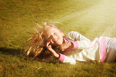 Happy girl. Happy little girl rolling down a grassy hill in the sunshine Royalty Free Stock Photography
