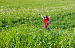 The happy girl. Walks on a green meadow in the summer Stock Photos