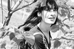 Happy girl. Black and white portrait of happy smiling brunette girl standing near tree among leaves on a bright sunny day Stock Images