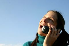 Happy girl. Young woman talking on a phone into a blue sky Royalty Free Stock Photo