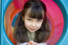 Happy girl. Looking girl on a playground royalty free stock photography