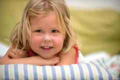 Happy Girl. Adorable little blond girl relaxing on pillow smiling Stock Image