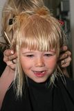 Happy girl. Professional hairdresser cutting childs hair, shild is smiling and having fun Stock Image