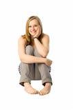Happy girl. Cute blonde teen sitting on floor Stock Photos