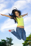 Happy girl. Young girl jumping in the view of the sky Stock Photos