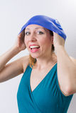Happy girl adjusts her swimming hat. In a bathing suit royalty free stock photos