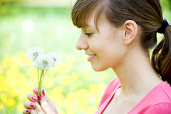 Happy girl admiring dandelions Royalty Free Stock Photography